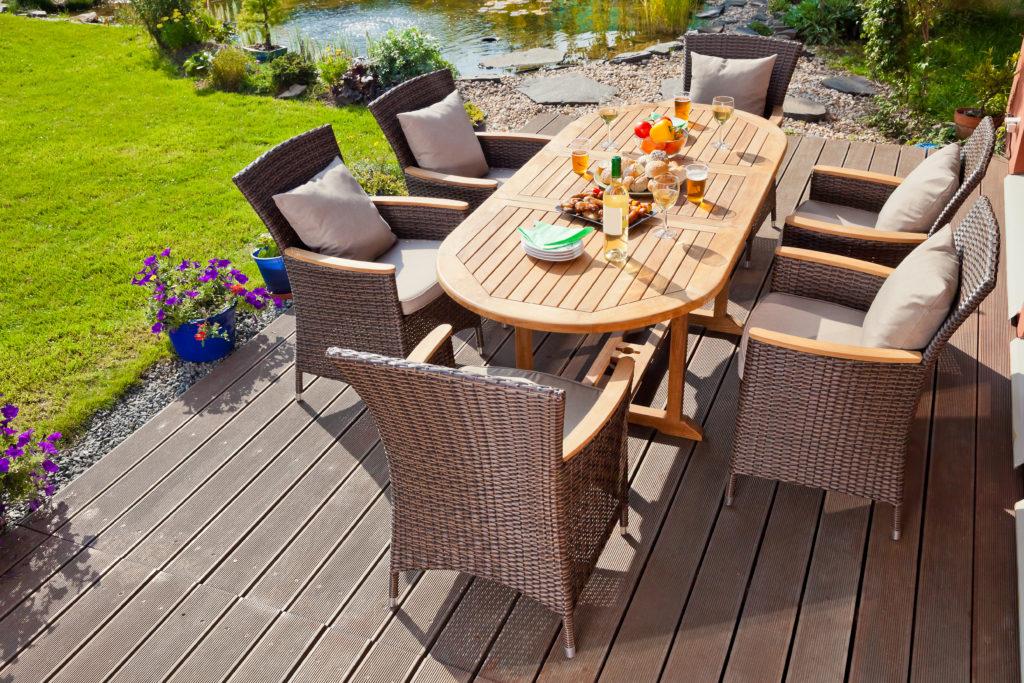 ratanové zahradní stoličky okolo dřevěného stolu na terase