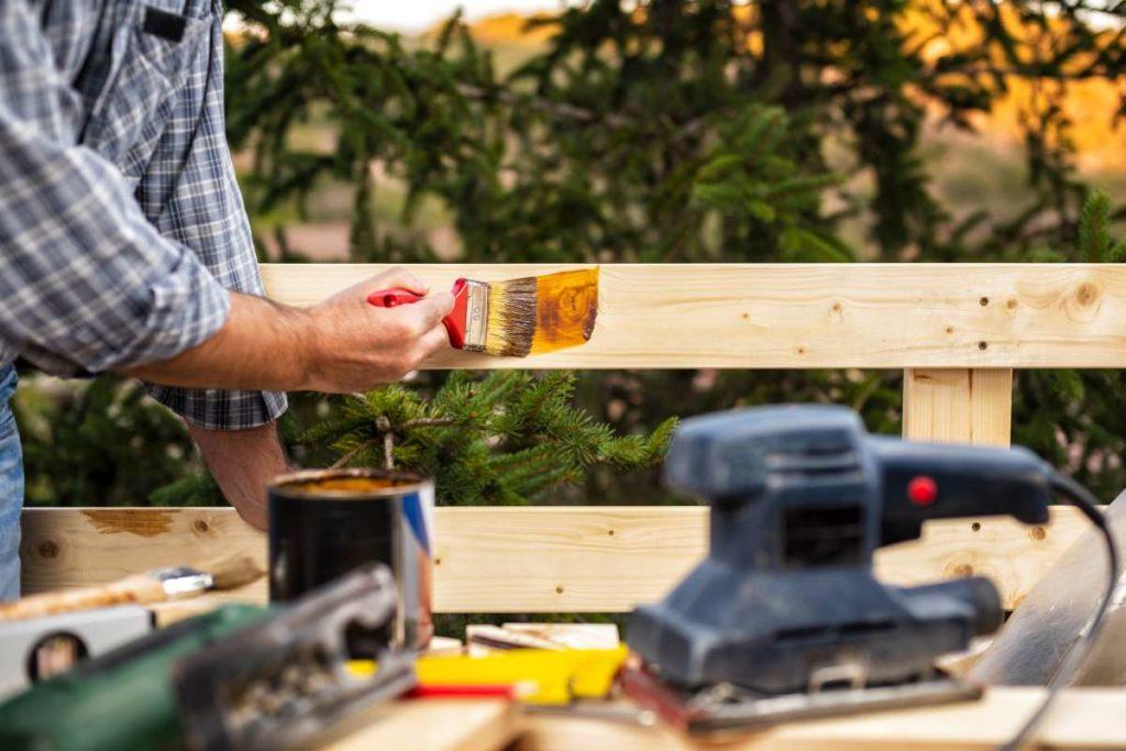 majster natírá štětcem impregnační nátěr na dřevo