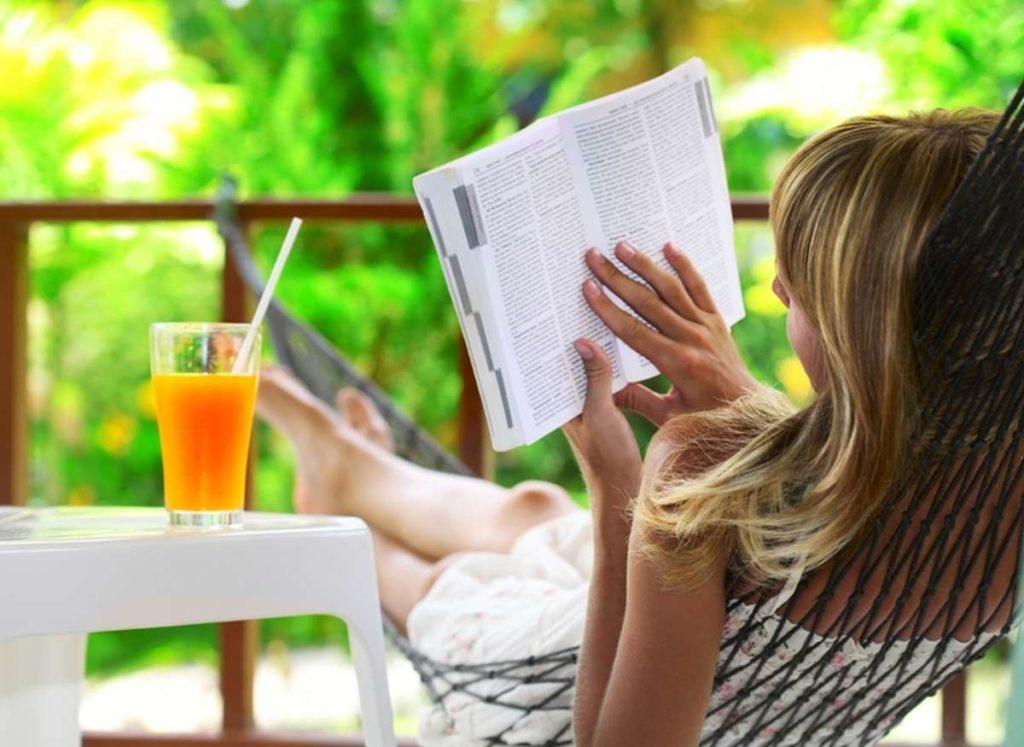 žena čtejíci si knížku na zahradě